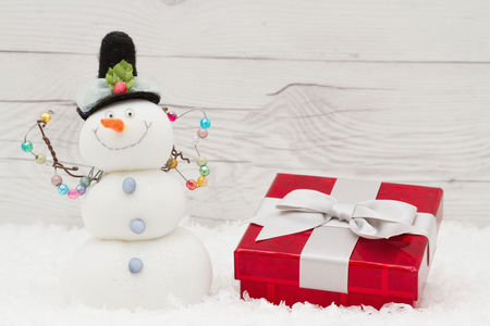 snowman wood: Christmas present and a snowman on weathered wood with copy space for message Stock Photo
