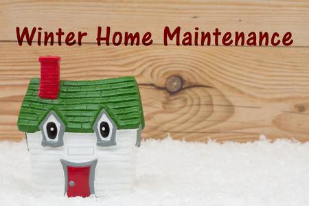 Una casa verde e rosso sulla neve e uno sfondo alterate legno con il testo Inverno Manutenzione Casa