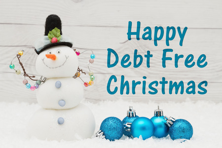 Some snow, Christmas ornaments and a snowman on weathered wood with text Happy Debt Free Christmas