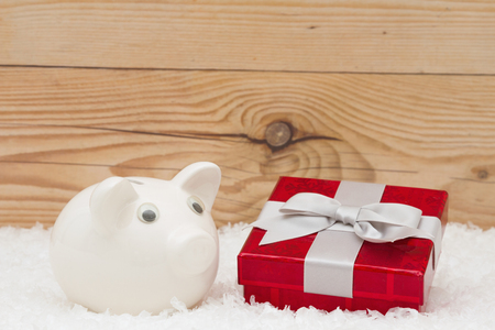 holiday spending: A white piggy bank with a red Christmas present on snow and a weathered wood background with copy space for message Stock Photo