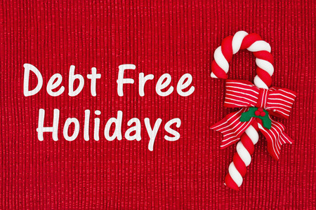 christmas debt: Christmas Debt Free message, Red shiny fabric with a candy cane with text Debt Free Holidays Stock Photo