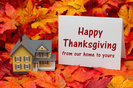 Some fall leaves and yellow and gray house and  greeting card with text Happy Thanksgiving from our home to yours