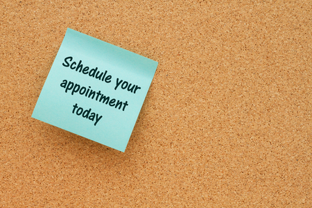 note board: Bulletin board with a blue sticky note with text Schedule your appointment today Stock Photo