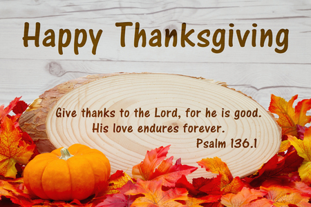 wood plaque: Happy Thanksgiving message, Some fall leaves, an alarm clock and wood plaque on weathered wood with text Psalm 136 Stock Photo