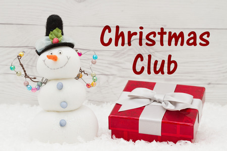 snowman wood: Some snow, Christmas present and a snowman on weathered wood with text Christmas Club Stock Photo