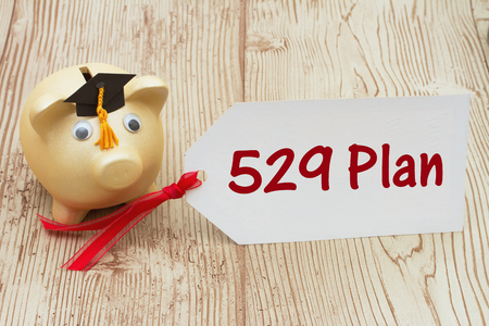 plan: Your 529 education savings plan, A golden piggy bank and grad cap on a desk with a gift tag with text 529 Plan Stock Photo