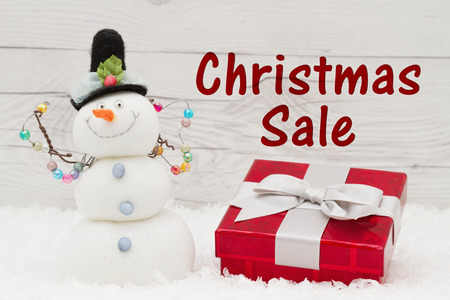 snowman wood: Holiday sale message, Some snow, Christmas present and a snowman on weathered wood with text Christmas Sale Stock Photo