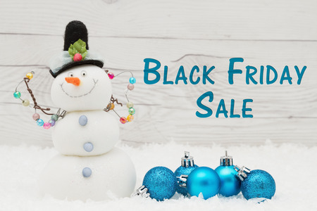 snowman wood: Some snow, Christmas ornaments and a snowman on weathered wood with text Black Friday Sale Stock Photo
