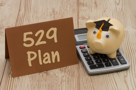post secondary schools: A golden piggy bank with grad cap on a calculator on a desk with text 529 plan