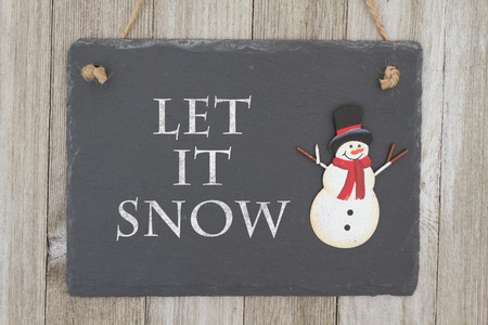 snowman wood: A retro chalkboard with a snowman hanging on weathered wood background with text Let it Snow Stock Photo