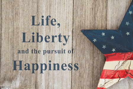 USA patriotic old flag on a star with weathered wood background with text Life, Liberty and the pursuit of Happiness