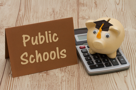 public schools: A golden piggy bank with grad cap on a calculator on a desk with text Public Schools
