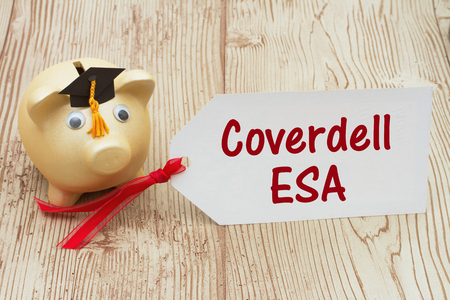 post secondary schools: A golden piggy bank and grad cap on a desk with a gift tag with text Coverdell ESA