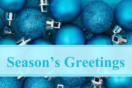 Enkele felblauwe sparkle en matte kerstbalversieringen met tekst Season's Greetings