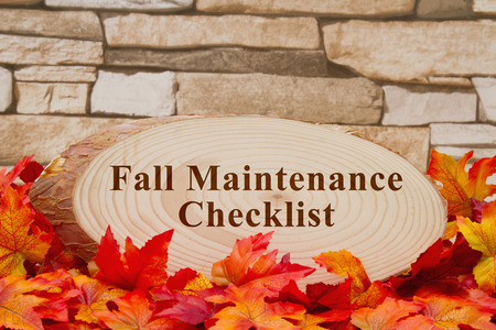 wood plaque: Some fall leaves, a pumpkin and wood plaque on weathered brick with text Fall Maintenance Checklist Stock Photo