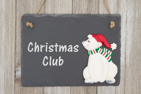 christmas budget: A retro chalkboard with a polar bear hanging on weathered wood background with text Christmas Club Stock Photo