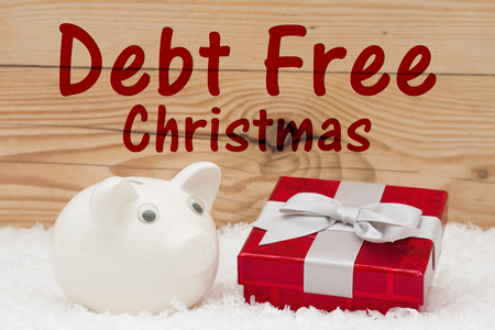 christmas debt: A white piggy bank with a red Christmas present on snow and a weathered wood background with text Debt Free Christmas Stock Photo