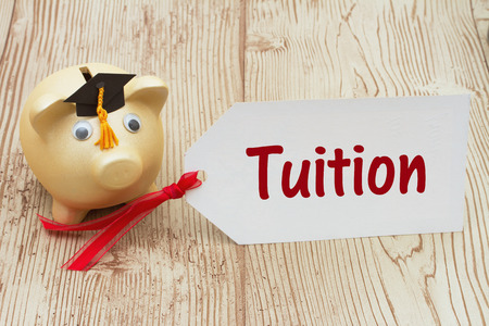post secondary schools: A golden piggy bank and grad cap on a desk with a gift tag with text Tuition