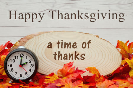 wood plaque: Some fall leaves, an alarm clock and wood plaque on weathered wood with text A time of Thanks Stock Photo
