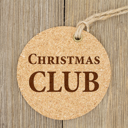 holiday budget: A retro round cork gift tag on weathered wood background with text Christmas Club