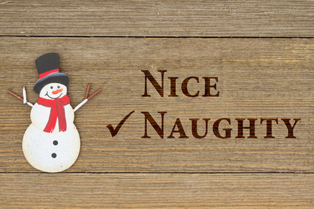 naughty or nice: A retro snowman on weathered wood background with text Nice Naughty