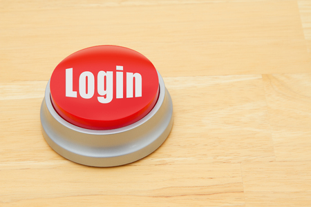A red and silver push button on a wooden desk with text Login