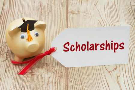 post secondary schools: A golden piggy bank and grad cap on a desk with a gift tag with text Scholarships
