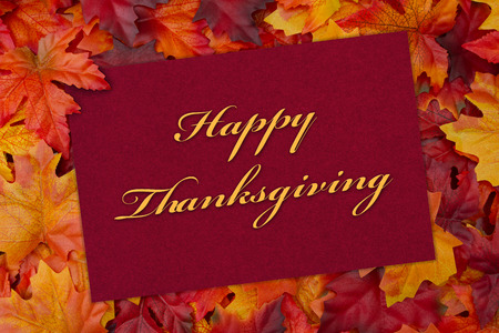 Some fall leaves and a greeting card with text Happy Thanksgiving Stock Photo