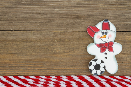 space wood: A retro soccer snowman on weathered wood background with copy space for message Stock Photo