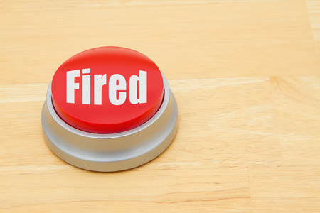 laidoff: A red and silver push button on a wooden desk with text Fired