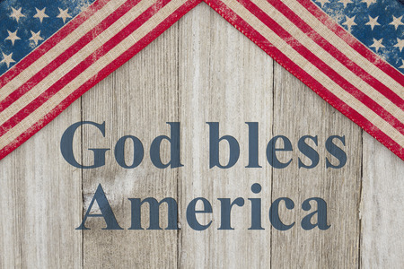 bless: USA patriotic old flag on a weathered wood background with text God Bless America