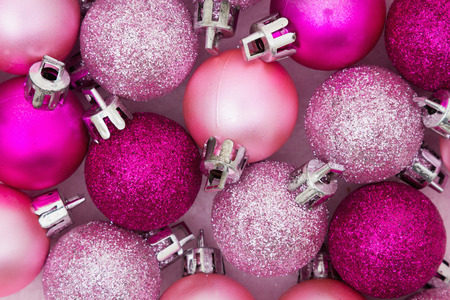 pink christmas: Some pale and bright pink sparkle and matte Christmas ball ornaments background Stock Photo