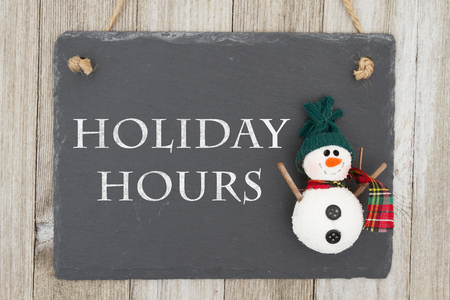 Old fashion Christmas store message, A retro chalkboard with a snowman hanging on weathered wood background with text Holiday Hours