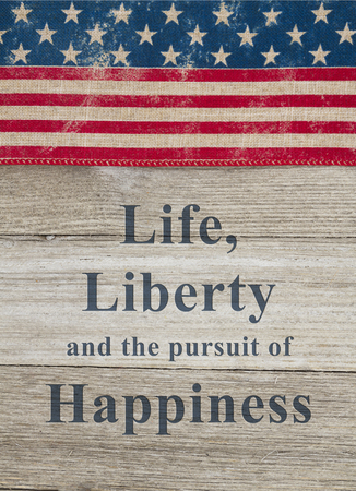 USA patriotic old flag on a weathered wood background with text Life, Liberty and the pursuit of Happiness