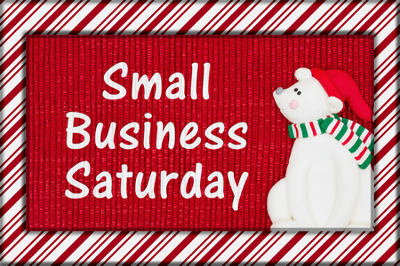 Red shiny fabric with a candy cane border and a Santa polar bear with text Small Business Saturday