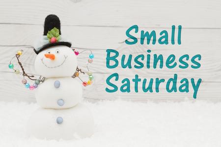 Qualche neve e un pupazzo di neve su legno esposto alle intemperie con testo Small Business sabato