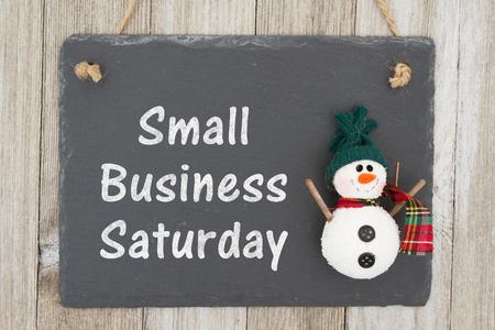 Una lavagna retrò con un pupazzo di neve appeso su fondo di legno stagionato con testo Small Business Sabato Archivio Fotografico
