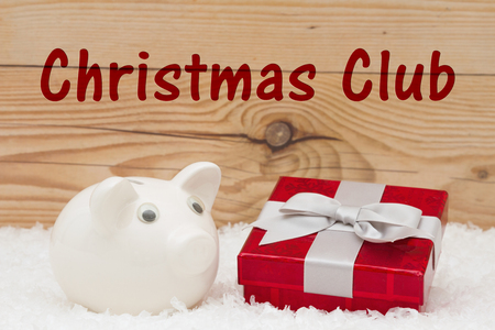 holiday budget: A white piggy bank with a red Christmas present on snow and a weathered wood background with text Christmas Club