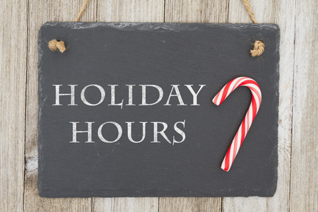 A retro chalkboard with a candy cane hanging on weathered wood background with text Holiday Hours
