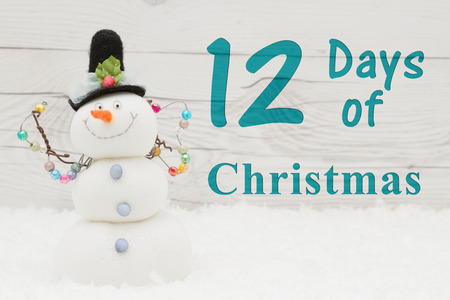 12 days of christmas: Some snow and a snowman on weathered wood with text 12 Days of Christmas Stock Photo