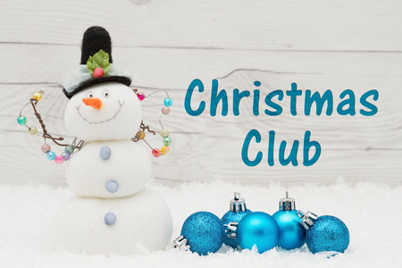 christmas budget: Some snow, Christmas ornaments and a snowman on weathered wood with text Christmas Club Stock Photo
