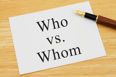 grammatical: Learning to use proper grammar, A white card on a desk with a pen with words Who vs Whom Stock Photo