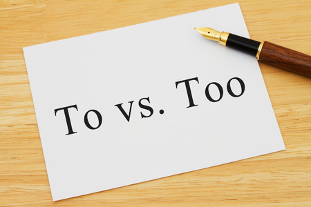 grammatical: A white card on a desk with a pen with words To vs Too