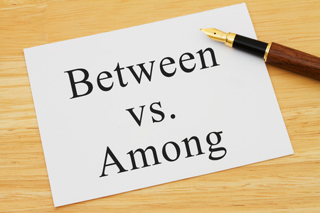 grammatical: A white card on a desk with a pen with words Between vs Among Stock Photo