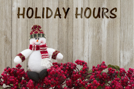 Old fashion Christmas store message, Frost covered red holly berries with a snowman on weathered wood background with text Holiday Hours Standard-Bild