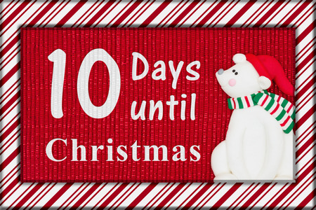 Christmas countdown message, Red shiny fabric with a candy cane border and a Santa polar bear with text 10 days until Christmas Banco de Imagens