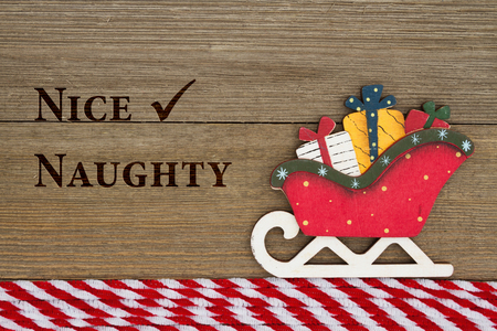 naughty or nice: Old fashion Christmas message, A retro Christmas sleigh on weathered wood background with text Nice and Naughty Stock Photo