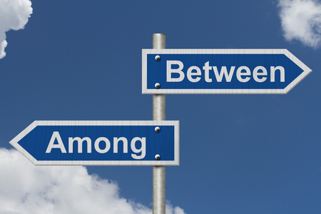grammatical: Learning to use proper grammar, Blue road sign with words Between and Among with sky background Stock Photo