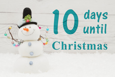 Christmas countdown message, Some snow and a snowman on weathered wood with text 10 days until Christmas Banco de Imagens