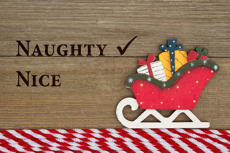naughty or nice: Old fashion Christmas message, A retro Christmas sleigh on weathered wood background with text Naughty and Nice Stock Photo